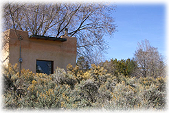 An adobe house on the outskirts of Taos, New Mexico, is surrounded by sagebrush and chamisa.